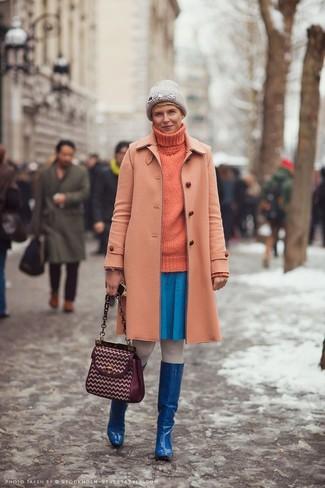 Wie kombinieren: orange Mantel, orange Strick Rollkragenpullover, blauer Skaterrock, blaue kniehohe Stiefel aus Leder