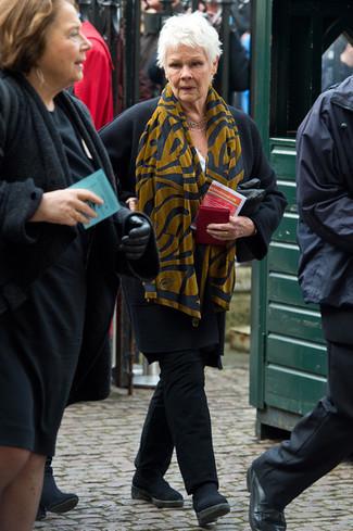 Wie kombinieren: schwarzer Mantel, schwarze Chinohose, schwarze Chelsea-Stiefel aus Wildleder, senf bedruckter Schal
