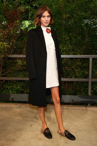 Wie kombinieren: schwarzer Mantel, weißes gerade geschnittenes Kleid, schwarze Leder Slipper, rote Anstecknadel mit Blumenmuster