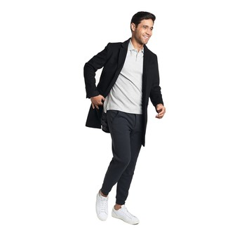 Wie kombinieren: schwarzer Mantel, graues Polohemd, schwarze Jogginghose, weiße Leder niedrige Sneakers