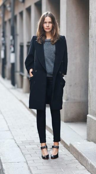 schwarzer Mantel, dunkelgrauer Pullover mit einem Rundhalsausschnitt, schwarze enge Hose, schwarze Leder Pumps für Damen
