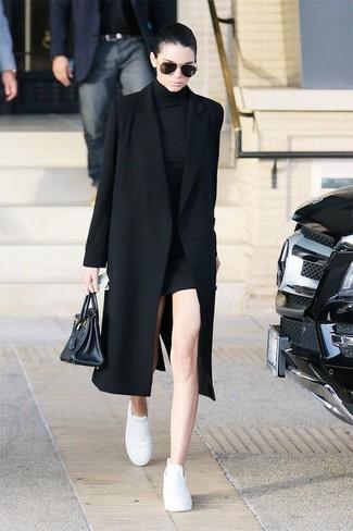 Kendall Jenner trägt Schwarzer Mantel, Schwarzes Sweatkleid, Weiße Leder Niedrige Sneakers, Schwarze Shopper Tasche aus Leder