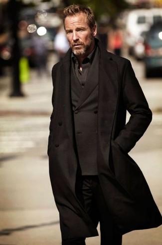 Rainer Andreesen trägt schwarzer Mantel, schwarzes Zweireiher-Sakko, schwarzes Langarmhemd, schwarze Jeans