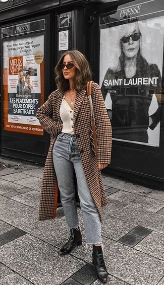 Wie kombinieren: brauner Mantel mit Karomuster, weiße Strickjacke, graue Jeans, schwarze Leder Stiefeletten
