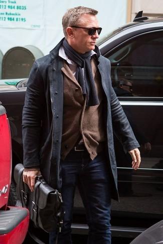 Die modische Kombination aus einem schwarzen Mantel und dunkelblauen Jeans ist perfekt für einen Tag im Büro.