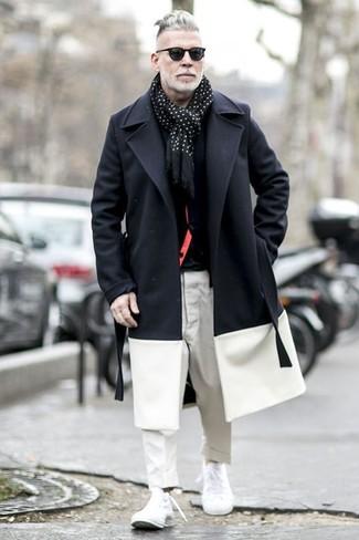 Wie kombinieren: schwarzer und weißer Mantel, schwarze Strickjacke, schwarzes T-Shirt mit einem Rundhalsausschnitt, weiße Chinohose