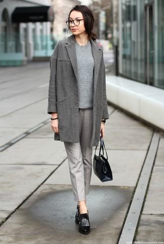 Wie kombinieren: grauer Mantel, grauer Strickpullover, graue Karottenhose, schwarze Leder Stiefeletten