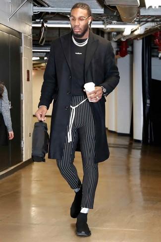 Wie kombinieren: schwarzer Mantel, schwarzes und weißes bedrucktes T-Shirt mit einem Rundhalsausschnitt, schwarze und weiße vertikal gestreifte Chinohose, schwarze Sportschuhe