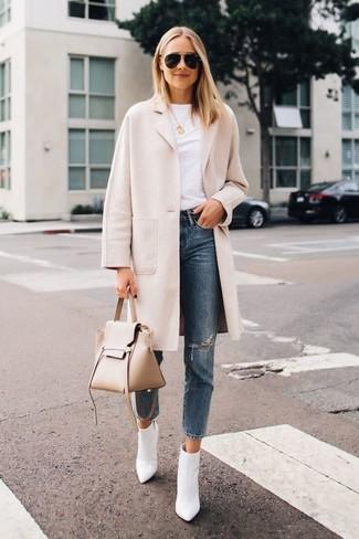 Wie kombinieren: hellbeige Mantel, weißes T-Shirt mit einem Rundhalsausschnitt, blaue Jeans mit Destroyed-Effekten, weiße Leder Stiefeletten