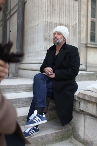 Schwarzen Mantel kombinieren: trends 2020: Paaren Sie einen schwarzen Mantel mit dunkelblauen Jeans für Ihren Bürojob. Wenn Sie nicht durch und durch formal auftreten möchten, vervollständigen Sie Ihr Outfit mit dunkelblauen und weißen Wildleder niedrigen Sneakers.