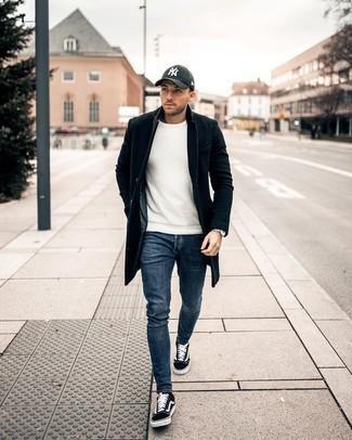Schwarzen Mantel kombinieren: trends 2020: Vereinigen Sie einen schwarzen Mantel mit blauen Jeans, um einen eleganten, aber nicht zu festlichen Look zu kreieren. Bringen Sie die Dinge durcheinander, indem Sie schwarzen und weißen Segeltuch niedrige Sneakers mit diesem Outfit tragen.