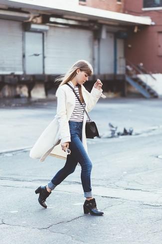 Wie kombinieren: weißer Mantel, weißes und schwarzes horizontal gestreiftes T-Shirt mit einem Rundhalsausschnitt, dunkelblaue Jeans, schwarze Leder Stiefeletten