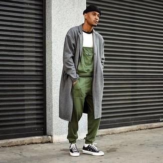 Wie kombinieren: grauer Mantel, weißes T-Shirt mit einem Rundhalsausschnitt, olivgrüne Latzhose, schwarze und weiße Segeltuch niedrige Sneakers