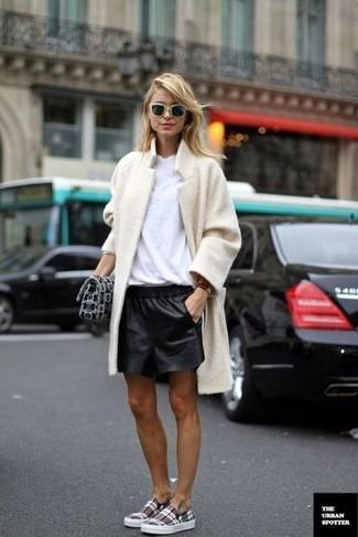 Wie kombinieren: hellbeige Fleece-Mantel, weißes T-Shirt mit einem Rundhalsausschnitt, schwarze Ledershorts, graue Slip-On Sneakers mit Schottenmuster