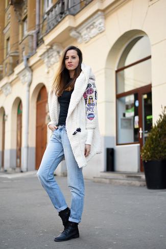 Wie kombinieren: weißer Fleece-Mantel, schwarze Langarmbluse, hellblaue Boyfriend Jeans, schwarze flache Stiefel mit einer Schnürung aus Leder