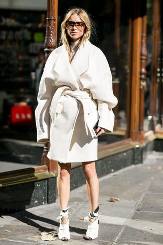 weißer Mantel, weißer Rollkragenpullover, weiße Leder Stiefeletten mit Ausschnitten, braune Sonnenbrille für Damen