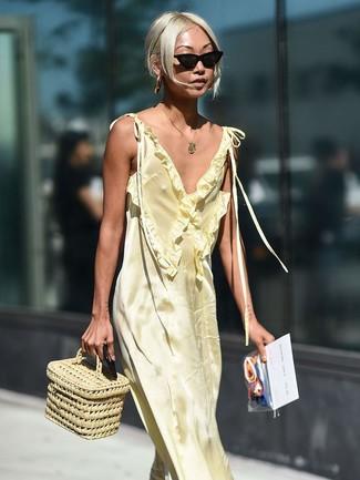 Wie kombinieren: gelbes Satin Maxikleid, hellbeige Strohhandtasche, schwarze Sonnenbrille, goldener Anhänger