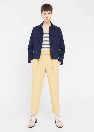 Wie kombinieren: dunkelblaue Militärjacke, weißes und schwarzes horizontal gestreiftes T-Shirt mit einem Rundhalsausschnitt, gelbe Karottenhose, weiße Leder Sandaletten