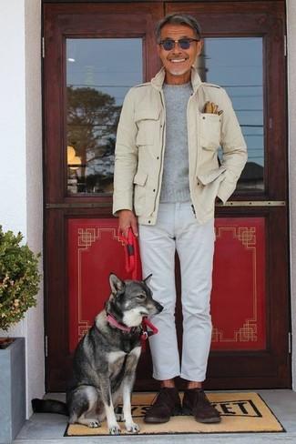 Wie kombinieren: hellbeige Militärjacke, grauer Pullover mit einem Rundhalsausschnitt, weiße Jeans, dunkelbraune Chukka-Stiefel aus Wildleder
