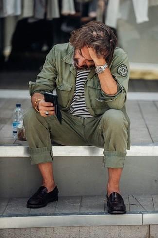 Wie kombinieren: olivgrüne Militärjacke, weißes und schwarzes horizontal gestreiftes T-Shirt mit einem Rundhalsausschnitt, olivgrüne Chinohose, schwarze Leder Slipper