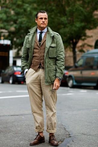 Wie kombinieren: olivgrüne Militärjacke, braune Wollweste, hellblaues Businesshemd mit Vichy-Muster, hellbeige Chinohose