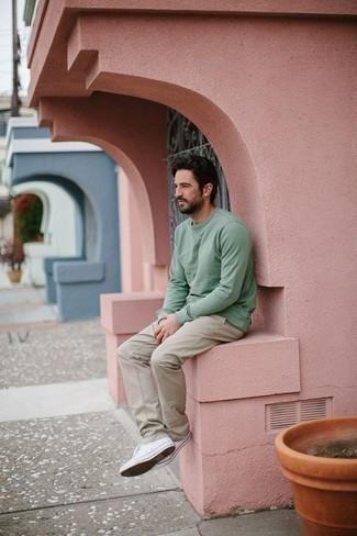 Herren Outfits 2020: Tragen Sie ein mintgrünes Langarmshirt und eine hellbeige Chinohose für einen bequemen Alltags-Look. Komplettieren Sie Ihr Outfit mit weißen Segeltuch niedrigen Sneakers.