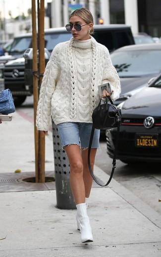 Wie kombinieren: weißer Strick Oversize Pullover, hellblaue Bermuda-Shorts aus Jeans, weiße Leder Stiefeletten, schwarze Leder Umhängetasche
