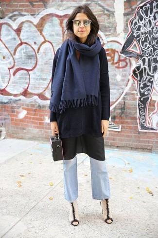 Wie kombinieren: schwarzer Oversize Pullover, schwarzes Camisole-Kleid, hellblaue Schlagjeans, weiße und schwarze Leder Stiefeletten