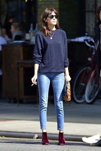 Alexa Chung trägt Dunkelblauer Oversize Pullover, Hellblaue Jeans, Dunkelrote Samt Stiefeletten, Beige Wildleder Clutch