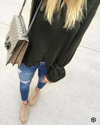 Wie kombinieren: dunkelgrüner Oversize Pullover, blaue enge Jeans mit Destroyed-Effekten, beige Wildleder Stiefeletten, hellbeige bedruckte Satchel-Tasche aus Segeltuch