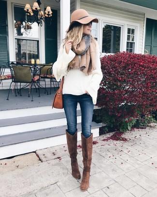 Wie kombinieren: weißer Strick Oversize Pullover, dunkelblaue enge Jeans, braune kniehohe Stiefel aus Wildleder, braune Leder Umhängetasche