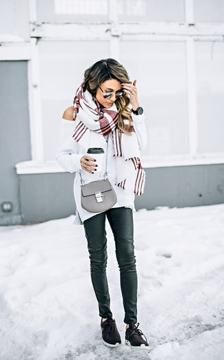 Wie kombinieren: weißer Oversize Pullover, schwarze Leder enge Jeans, dunkelbraune Sportschuhe, graue Leder Umhängetasche
