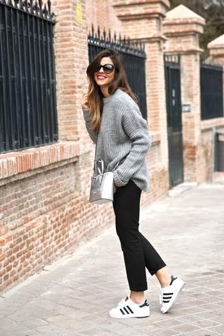 Wie kombinieren: grauer Strick Oversize Pullover, schwarze Chinohose, weiße und schwarze Leder niedrige Sneakers, silberne Leder Umhängetasche