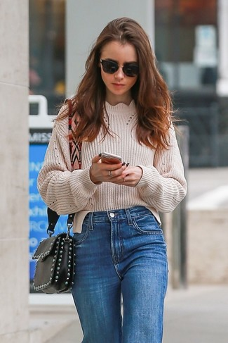 Wie kombinieren: hellbeige Strick Oversize Pullover, blaue Jeans, schwarze verzierte Leder Umhängetasche, schwarze Sonnenbrille