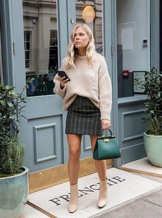 Wie kombinieren: hellbeige Strick Oversize Pullover, dunkelgrauer Minirock mit Karomuster, hellbeige Leder Stiefeletten, dunkelgrüne Shopper Tasche aus Leder