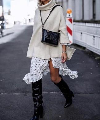 Wie kombinieren: hellbeige Strick Oversize Pullover, weißes und schwarzes gepunktetes Wickelkleid, schwarze kniehohe Stiefel aus Leder, schwarze gesteppte Leder Umhängetasche