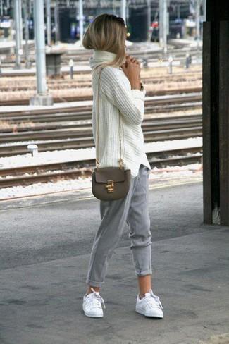 Wie kombinieren: weißer Strick Oversize Pullover, graue Karottenhose, weiße niedrige Sneakers, olivgrüne Leder Umhängetasche