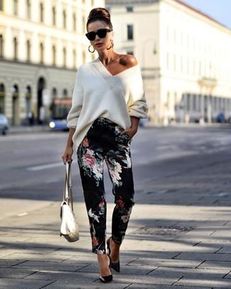 Wie kombinieren: weißer Strick Oversize Pullover, schwarze Karottenhose mit Blumenmuster, schwarze Leder Pumps, weiße gesteppte Satchel-Tasche aus Leder