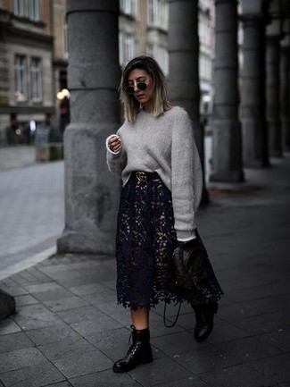 Wie kombinieren: grauer Oversize Pullover, schwarzer Midirock aus Spitze, schwarze flache Stiefel mit einer Schnürung aus Leder, schwarzer bedruckter Leder Rucksack