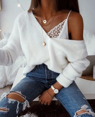 Wie kombinieren: weißer Strick Oversize Pullover, weißes Spitze Trägershirt, blaue Jeans mit Destroyed-Effekten, goldener Anhänger