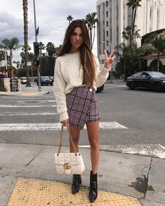 Damen Outfits 2020: Paaren Sie einen weißen Strick Oversize Pullover mit einem rosa Tweed Minirock, umeinen stylischen Alltags-Look zu erhalten, der im Kleiderschrank der Frau nicht fehlen darf. Ergänzen Sie Ihr Look mit schwarzen Leder Stiefeletten.