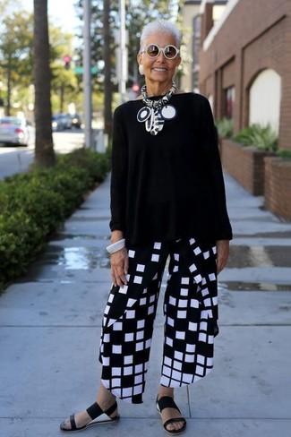 Wie kombinieren: schwarzer Oversize Pullover, schwarze und weiße weite Hose mit Karomuster, schwarze flache Sandalen aus Leder, weiße Sonnenbrille