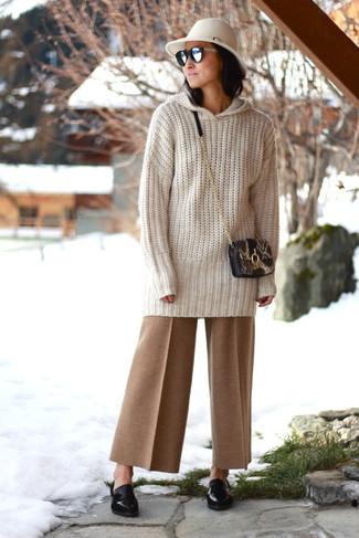 Wie kombinieren: hellbeige Strick Oversize Pullover, beige weite Hose, schwarze Leder Slipper, schwarze Leder Umhängetasche mit Schlangenmuster
