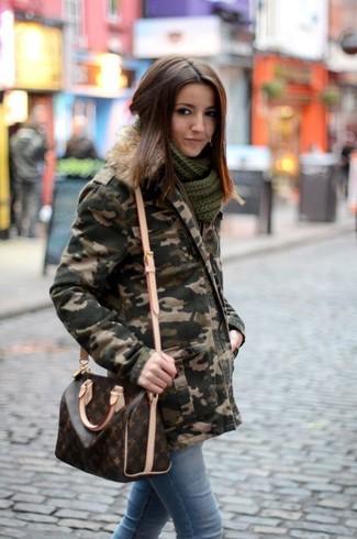 Wie kombinieren: dunkelgrüner Camouflage Parka, hellblaue enge Jeans, dunkelbraune bedruckte Leder Umhängetasche, dunkelgrüner Strick Schal