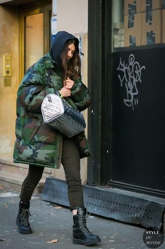Wie kombinieren: dunkelgrüner Camouflage Parka, schwarzer Pullover mit einer Kapuze, olivgrüne bedruckte enge Jeans, schwarze flache Stiefel mit einer Schnürung aus Leder