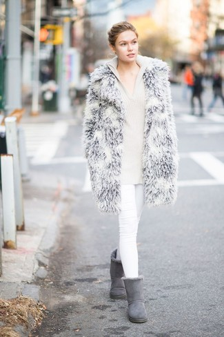 Wie kombinieren: grauer Pelz, hellbeige Strick Pullover mit einer Kapuze, weiße enge Jeans, graue Ugg Stiefel
