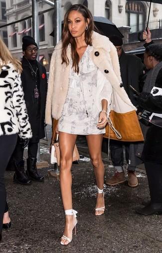 Wie kombinieren: hellbeige Pelz, weißes gerade geschnittenes Kleid mit Blumenmuster, weiße Leder Sandaletten, beige Satchel-Tasche aus Leder