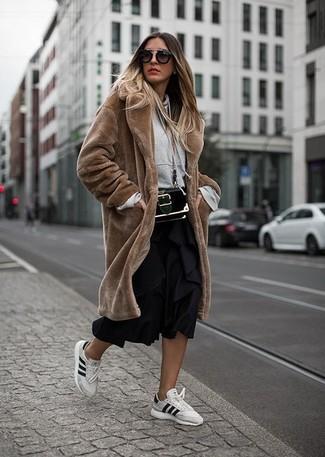 Wie kombinieren: brauner Pelz, grauer Pullover mit einer Kapuze, schwarzer Falten Midirock, weiße Leder niedrige Sneakers