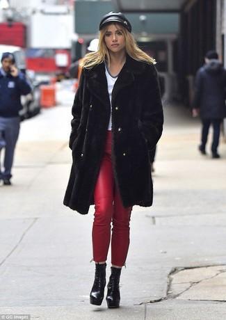 Wie kombinieren: schwarzer Pelz, weißes T-Shirt mit einem V-Ausschnitt, rote Leder enge Jeans, schwarze klobige Schnürstiefeletten aus Leder