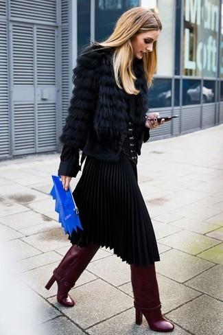 Olivia Palermo trägt schwarze Pelzjacke, schwarze Bluse mit Knöpfen, schwarzer Falten Midirock, dunkelrote kniehohe Stiefel aus Leder